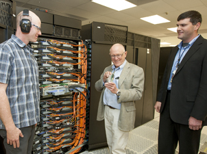 Three people in front of Sequoia super computer