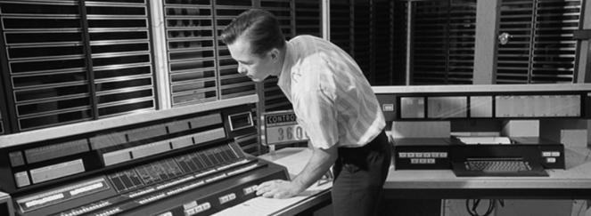 PIcture of a 1960s supercomputer and operator
